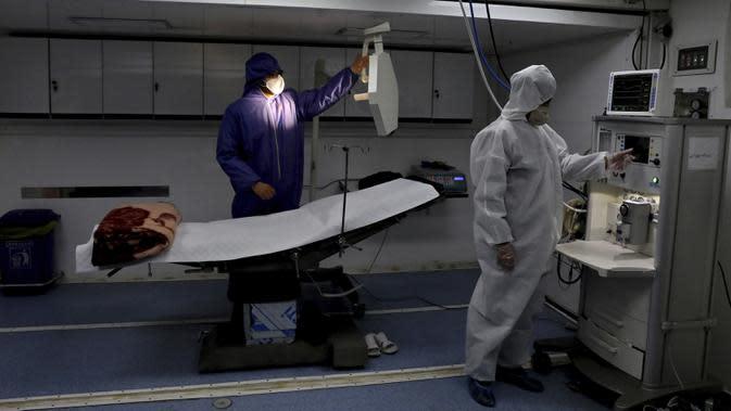 Petugas berpakaian pelindung bekerja di rumah sakit sementara khusus pasien virus corona COVID-19 di Teheran, Iran, Kamis (26/3/2020). Kementerian Kesehatan dan Pendidikan Kedokteran Iran mengatakan, satu warga Iran meninggal akibat virus corona COVID-19 setiap 12 menit. (AP Photo/Ebrahim Noroozi)