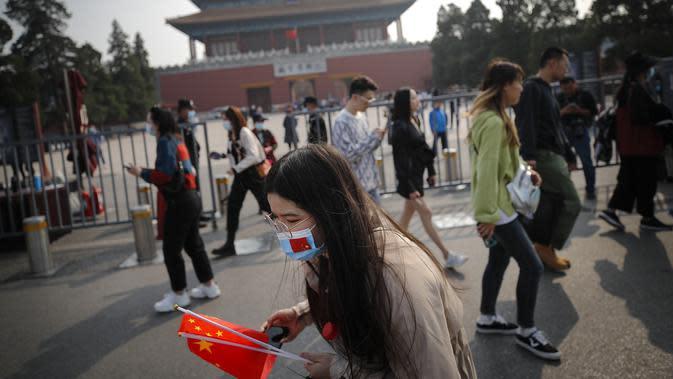 Seorang wanita mengenakan masker untuk mencegah penyebaran virus corona memegang bendera nasional Kota Terlarang selama Hari Nasional di Beijing, Rabu, (7/10/2020). Turis Tiongkok melakukan 425 juta perjalanan domestik pada paruh pertama dari delapan hari libur Hari Nasional. (AP Photo/Andy Wong)