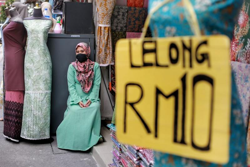 A worker waits for customers in front of a fabric store on Jalan Masjid India amid the conditional movement control order in Kuala Lumpur May 7, 2020. — Picture by Ahmad Zamzahuri