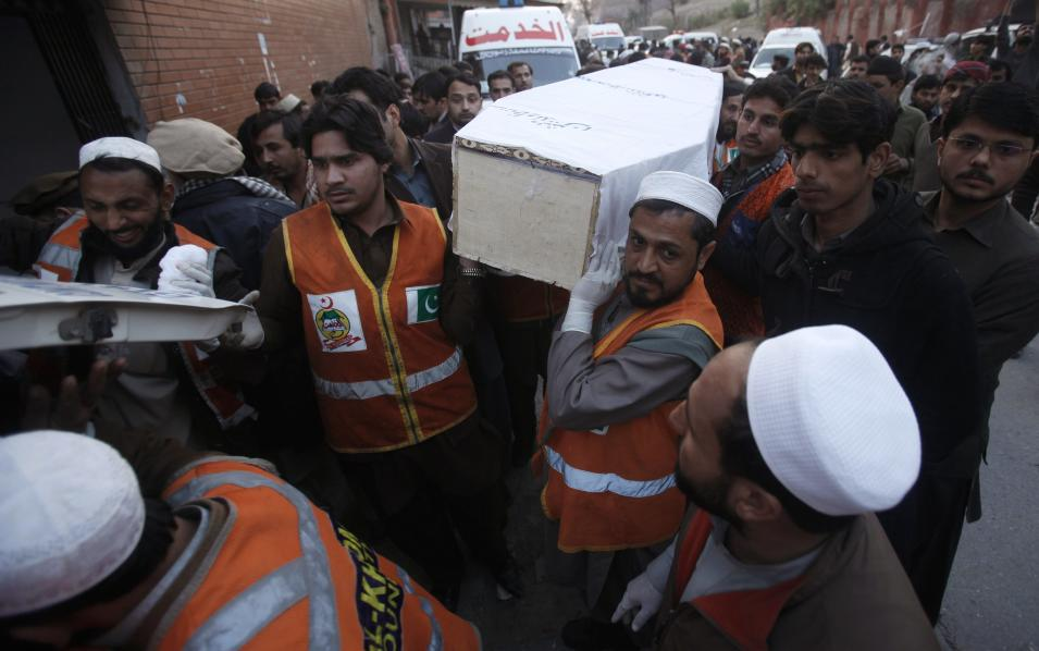 Rescue workers carry the casket of a man, who was killed in a grenade attack, from a hospital morgue to an ambulance in Peshawar