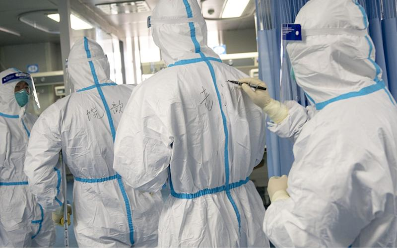 Medical workers write names on each other's protective suits for recognition in Zhongnan Hospital of Wuhan University in Wuhan, central China's Hubei Province - REX