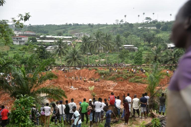 People look at the site of a landslide that killed at least 13 people in Anyama, a suburb of Abidjan