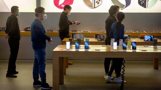 Para pekerja mengenakan masker saat menjaga Apple Store yang dibuka kembali di Beijing, China, Jumat (14/2/2020). Sejauh ini dikabarkan baru lima Apple Store yang dibuka kembali di China. (AP Photo/Mark Schiefelbein)