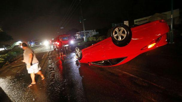 PHOTO: People tend to a car that flipped over on Cape Coral Parkway during Hurricane Irma, in Cape Coral, Fla., Sept. 10, 2017. (Gerald Herbert/AP)