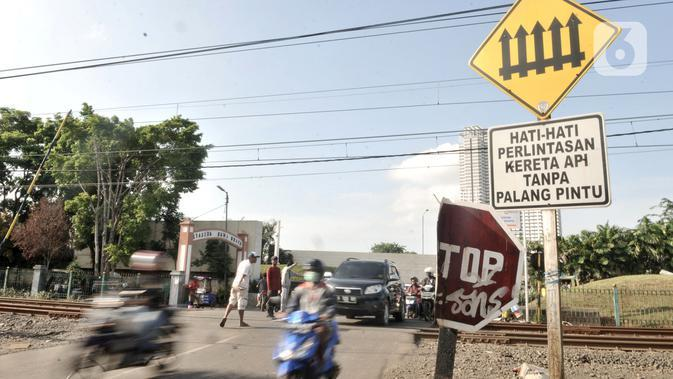Kendaraan melintasi perlintasan kereta api di Jalan Duri Kosambi Raya, Jakarta, Rabu (15/1/2020). Warga setempat membangun palang secara swadaya dan mengatur lalu lintas akibat perlintasan kereta dekat Stasiun Rawa Buaya tersebut belum dipasang palang pintu otomatis. (merdeka.com/Iqbal Nugroho)