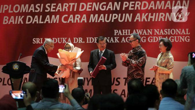 Wakil Presiden ke-10 dan ke-12 RI Jusuf Kalla (tengah) saat menerima anugerah dari Pembina Yayasan Sekar Manggis Anak Agung Gde Agung (kiri) saat penyerahan penghargaan Anugerah Dr Ide Anak Agung Gde Agung di Kantor Kementerian Luar Negeri, Jakarta, Kamis (23/1/2020). (Liputan6.com/Faizal Fanani)