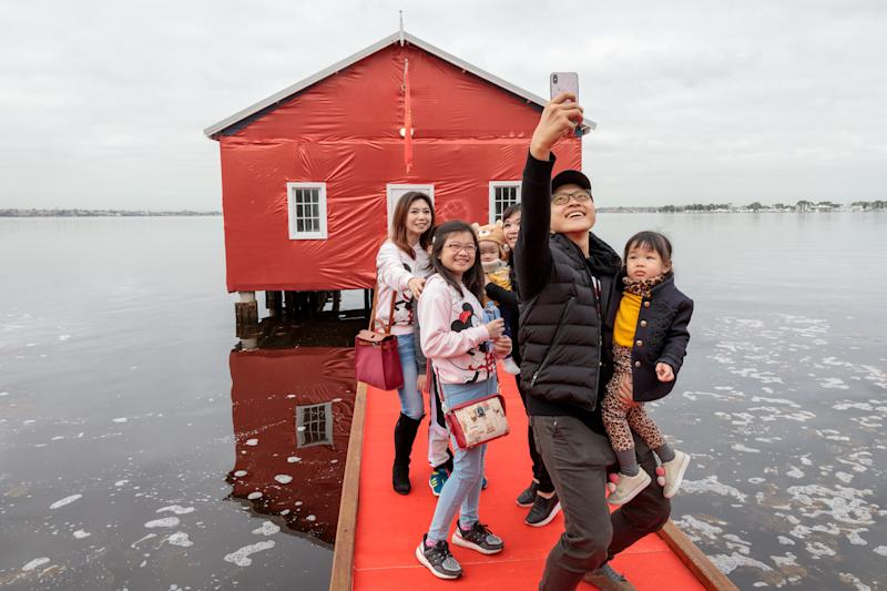Members of the public take pictures of the Crawley boatshed on the Swan river which has been covered in red to celebrate the arrival of Manchester United Football Club in Perth.
