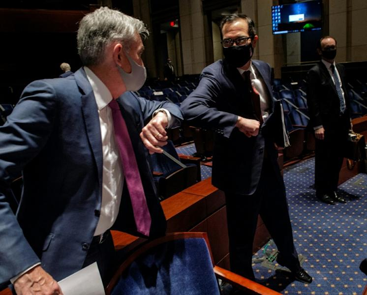 Fed Chair Jerome Powell (L) and Treasury Secretary Stephen Mnuchin bump elbows after a hearing where Powell said keeping COVID-19 in check is a key step to economic recovery