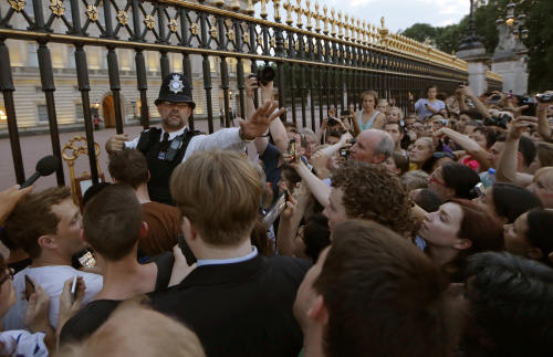 A police officer tries to control a crowd of people trying to get to the railing to take pictures of a notice proclaiming the birth of a baby boy to Prince William and Kate, Duchess of Cambridge on display for public view at Buckingham Palace in London, Monday, July 22, 2013. (AP Photo/Sang Tan)
