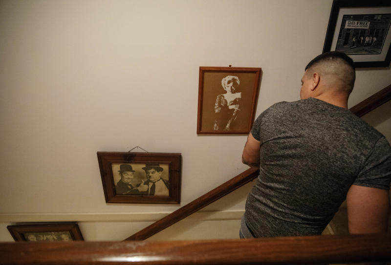 Yasnier Palacio Nieves, an asylum seeker from Cuba, walks past photos of Laurel and Hardy and Marilyn Monroe that hang on the wall of a local resident who opens her home to immigrant detainees released at night from the rural Stewart Detention Center, Wednesday, Nov. 6, 2019, in Columbus, Ga. (AP Photo/David Goldman)