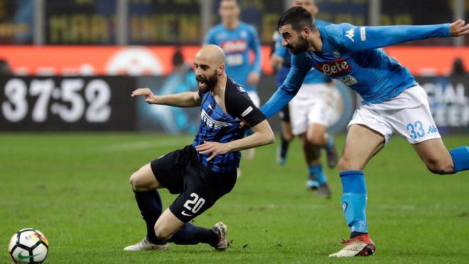 Pemain Napoli, Raul Albiol menarik jersey pemain Inter Milan, Borja Valero saat berebut bola dalam lanjutan Serie A di Giuseppe Meazza, Senin (12/3). Inter Milan dan Napoli harus puas berbagi angka dengan skor akhir 0-0. (AP/Luca Bruno)