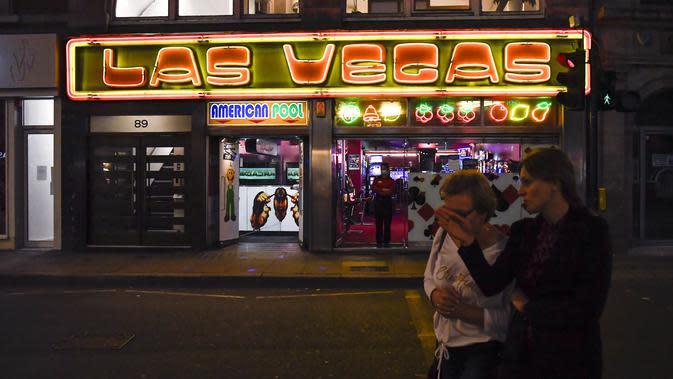 Orang-orang berjalan melewati kasino di Soho, di London, Selasa (22/9/2020). Perdana Menteri Inggris, Boris Johnson, telah mengumumkan bahwa pub dan restoran tutup pada pukul 10 malam, karena lonjakan kasus virus corona di seluruh Inggris. (AP Photo / Alberto Pezzali)