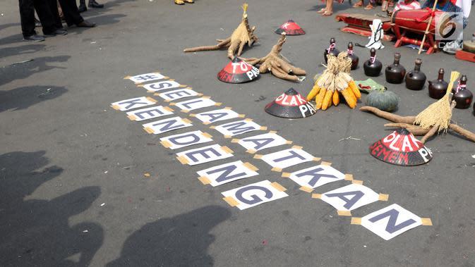Tulisan #selamatkan kendeng terpampang saat aksi di depan Istana Negara, Jakarta, Kamis (2/8). Dalam aksinya, mereka melakukan tradisi Brokohan memperingati pertemuan mereka dengan Presiden Jokowi. (Liputan6.com/Helmi Fithriansyah)