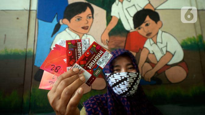 Guru memperlihatkan dua kartu perdana Tri dan Telkomsel beserta kuota gratis yang dibagikan kepada wali murid di SDN Serua Indah I dan II, Ciputat, Tangerang Selatan, Senin (15/9/2020). Program Kartu Perdana itu untuk mendukung kegiatan belajar secara online saat covid-19. (merdeka.com/Dwi Narwoko)