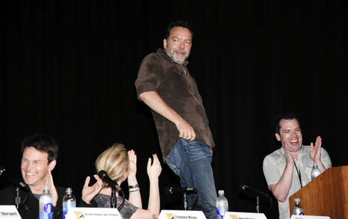 Director Alan Ball stands on a chair as he rolls his belly as actor Stephen Moyer, far left, actress Anna Paquin, left, and moderator Tim Stack, right, look on during the True Blood panel on the third day of Comic-Con convention held at the San Diego Convention Center on Saturday, July 14, 2012, in San Diego. (Photo by Denis Poroy/Invision/AP)