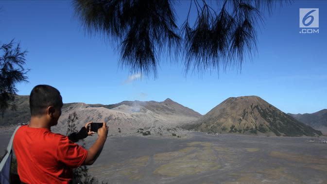 Seorang wisatawan mengambil gambar Gunung Bromo, Probolinggo, Jawa Timur, Minggu (8/7). Kementerian Pariwisata menargetkan kunjungan 20 juta wisatawan mancanegara dan 375 juta pergerakan wisatawan Nusantara pada 2020. (Liputan6.com/Arya Manggala)