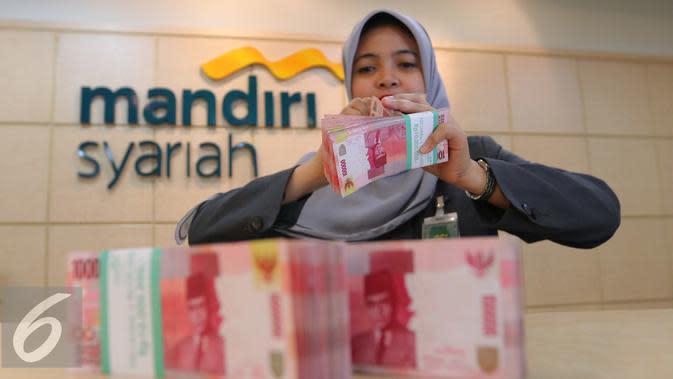 Petugas menghitung uang di Bank Mandiri Syariah, Jakarta, Kamis (14/7). Otoritas Jasa Keuangan (OJK) memastikan hanya bank syariah besar yang dilibatkan dalam pelaksanaan kebijakan pengampunan pajak. (Liputan6.com/Angga Yuniar)