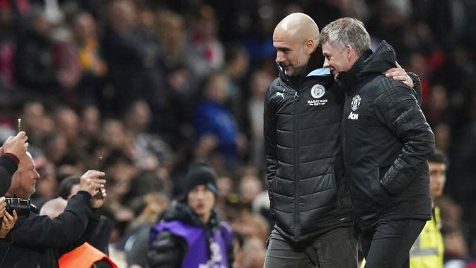Pelatih Manchester City, Pep Guardiola berbincang dengan pelatih Manchester United, Ole Gunnar Solskjaer, pada laga Piala Liga Inggris di Stadion Old Trafford, Rabu (8/1/2020). Manchester United kalah 1-3 dari Manchester City. (AP/Jon Super)