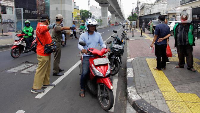 Pengendara motor pergi seusai diberi hukuman push up karena tidak memakai masker saat razia Pembatasan Sosial Berskala Besar (PSBB) di Kawasan Jalan Fatmawati, Jakarta, Selasa (28/4/2020). Penertiban terkait pelaksanaan PSBB Jakarta dan memutus rantai penyebaran COVID 19. (merdeka.com/Imam Buhori)