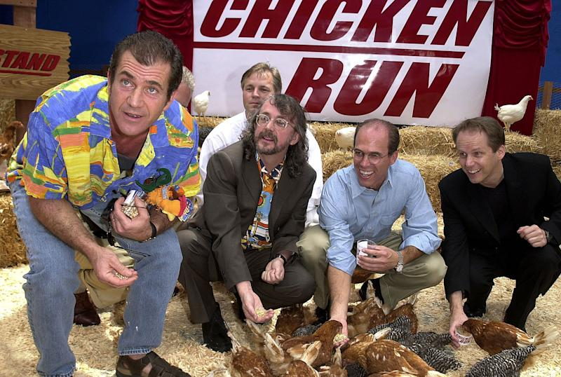 "UNIVERSAL CITY, UNITED STATES: US actor Mel Gibson (L) feeds chickens at the premiere of new British animated film ""Chicken Run"" for which he provides the voice of Rocky the rooster, as British directors Peter Lord (2nd L) and Nick Park (R), and executive producer Jeffrey Katzenberg (2nd R) look on, in Universal City, CA 17 June, 2000. (ELECTRONIC IMAGE) AFP PHOTO/Lucy NICHOLSON (Photo credit should read LUCY NICHOLSON/AFP via Getty Images)"