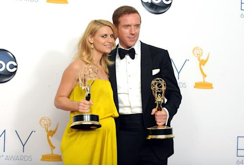"Actress Claire Danes, winner of the Emmy for outstanding lead actress in a drama series for ""Homeland,"" left, and actor Damien Lewis, winner of the Emmy for outstanding lead actor in a drama series for ""Homeland"" pose together backstage at the 64th Primetime Emmy Awards at the Nokia Theatre on Sunday, Sept. 23, 2012, in Los Angeles. (Photo by Jordan Strauss/Invision/AP)"
