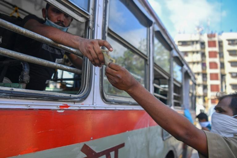 A migrant worker gets change after buying ticket from Dharavi slum to take them to a railway station in Mumbai