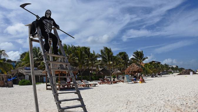 Seorang pria muda yang menyamar sebagai malaikat maut berada di pantai Puerto Morelos di Puerto Morelos, Quintana Roo, Meksiko, Sabtu (1/8/2020). Pria itu meminta wisatawan dan penduduk setempat kembali ke rumah karena pantai masih tertutup bagi pengunjung di tengah COVID -19. (ELIZABETH RUIZ/AFP)
