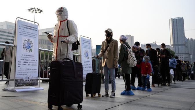 Warga yang mengenakan alat pelindung diri tiba di Stasiun Hankou, Wuhan, Hubei, China, Rabu (8/4/2020). Setelah pandemi virus corona COVID-19 mereda, banyak warga di Wuhan beraktivitas memakai masker, sarung tangan, pelindung wajah, hingga pakaian pelindung. (NOEL CELIS/AFP)