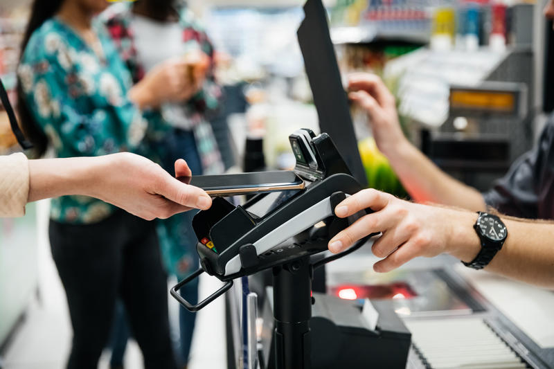 A close up of a contactless payment being made using a smartphone at the supermarket.