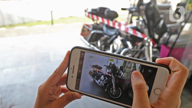 Layar ponsel mengambil gambar motor Harley Davidson milik tersangka Jiwasraya yang terparkir di Kejaksaan Agung, Kamis (16/1/2020). Kejagung menyita kendaraan dari tersangka dugaan korupsi Jiwasraya berupa enam mobil berbagai merk dan motor Harley Davidson. (Liputan6.com/Herman Zakharia)