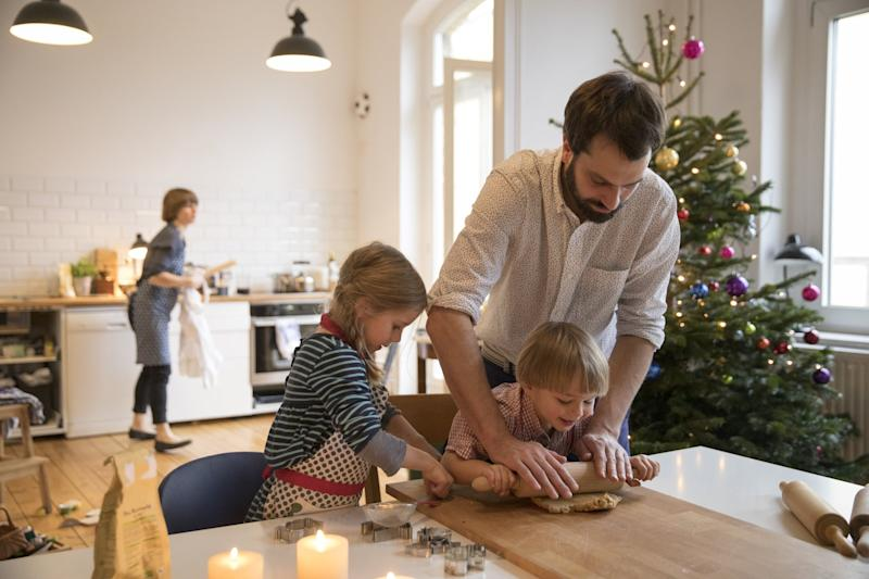 Caucasian father preparing cookies with todller girl and boy at table in living room