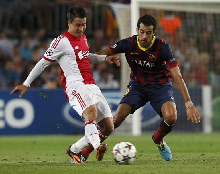 Ajax's Krkic and Barcelona's Busquets fight for the ball during their Champions League soccer match at Camp Nou stadium in Barcelona