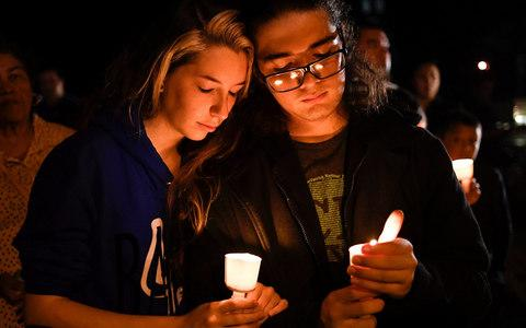 Local residents take part in a candle light vigil for victims of a mass shooting in Sutherland Springs - Credit: REUTERS/Mohammad Khursheed