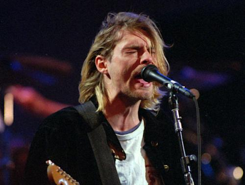 "FILE - This Dec. 13, 1993 file photo shows Kurt Cobain of the Seattle band Nirvana performing in Seattle, Wash. After hearing from Kurt Cobain and Nirvana fans across the United States, the Washington state city of Aberdeen is keeping the words ""Come as you are"" on a welcome sign. KBKW and KXRO report Mayor Bill Simpson announced at Wednesday night's City Council meeting the sign will stay. The mayor received more than 300 emails after reports that the reference to a Nirvana song would be dropped when the sign is replaced. ""Come as you are"" was added to the ""Welcome to Aberdeen"" sign in 2005 following the 10-year anniversary of Cobain's 1994 death in Seattle. Cobain grew up in Aberdeen. (AP Photo/Robert Sorbo, file)"