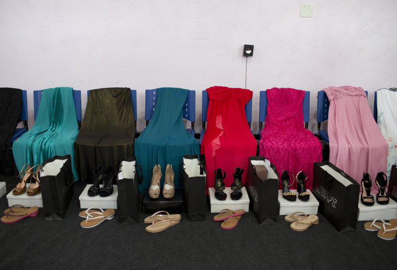 Gowns and shoes are laid out for female inmates who are competing in the 13th annual Miss Talavera Bruce beauty pageant, the namesake of the female prison in western Rio de Janeiro, Brazil, Tuesday, Dec. 4, 2018. For a day, about a dozen women serving time at the penitentiary swap their uniforms for gowns. The clothes the contestants compete in are on loan from a local business. (AP Photo/Silvia Izquierdo)