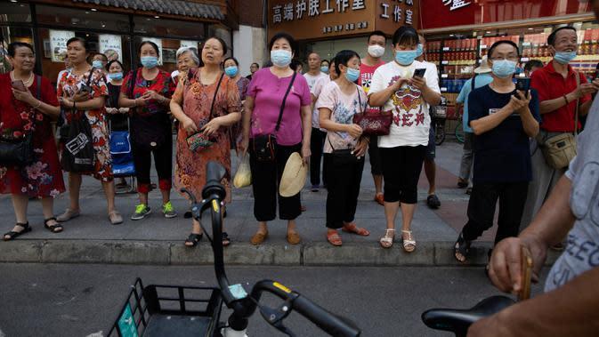 Penutupan Konsulat AS Jadi Tontonan: Orang-orang berkumpul saat pihak berwenang China bersiap untuk memasuki Konsulat AS di Chengdu, Senin (27/7/2020). Bendera Amerika Serikat di Konsulat AS Chengdu diturunkan menandai ditutupnya kantor perwakilan Negeri Paman Sam di kota itu. (AP Photo/Ng Han Guan)