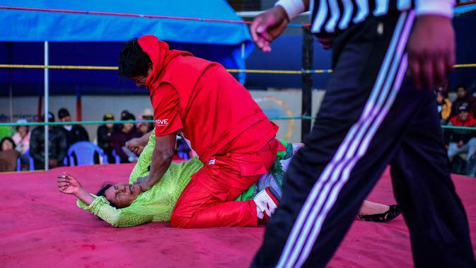 Pegulat Bolivia, Lidia Flores dikunci oleh lawannya pegulat pria di atas ring gulat di El Alto, pada 24 November 2019. Di Bolivia ada sebuah atraksi gulat yang diperankan perempuan dengan menggunakan busana khas warga Bolivia. (Ronaldo SCHEMIDT / AFP)