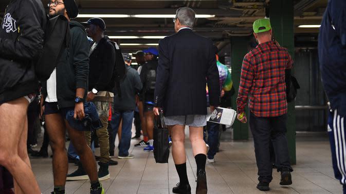 Peserta acara tahunan No Pants Subway Ride menunggu untuk menaiki kereta di stasiun bawah tanah di New York pada Minggu (12/1/2020). New York menjadi kota pertama yang menghajat acara naik kereta tanpa celana ini sejak tahun 2002. (Johannes EISELE / AFP)