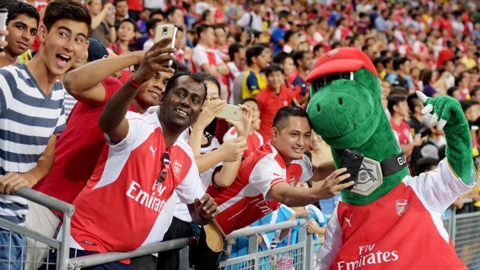 Sosok di balik boneka dinosaurus tersebut adalah pria bernama Jerry Quy. Gunnersaurus telah menjadi maskot klub Arsenal selama 27 tahun. (AP Photo/Joseph Nair)