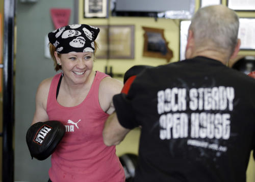 Kristy Rose Follmar spars with a class participant during a workout at Rock Steady Boxing in Indianapolis, Tuesday, April 9, 2013. Rock Steady boxing is a unique nonprofit gym that, since 2006, has offered a uniquely effective form of physical exercise to people who are living with Parkinson's. (AP Photo/Michael Conroy)