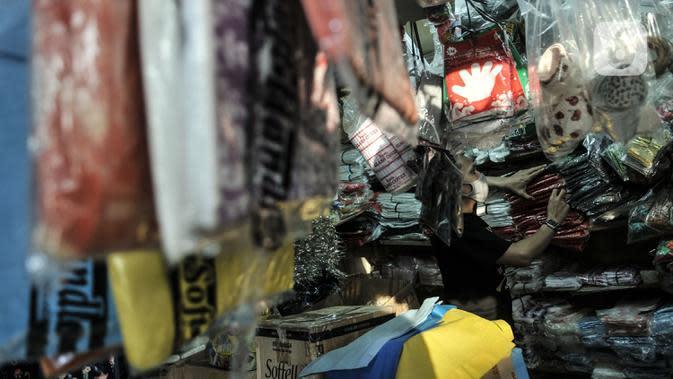 Abdullah (37) merapikan kantong plastik sekali pakai yang dijualnya di Pasar Tebet Barat, Jakarta, Selasa (30/6/2020). Jelang pemberlakuan larangan penggunaan plastik sekali pakai, Abdullah mengaku penjualan kantong kresek di tokonya menurun hingga 30 persen. (merdeka.com/Iqbal S Nugroho)