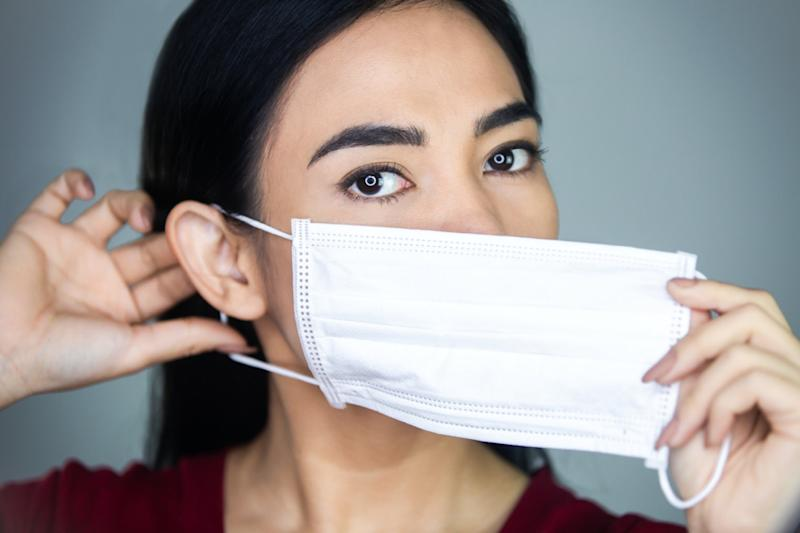 woman putting on a medical disposable mask.
