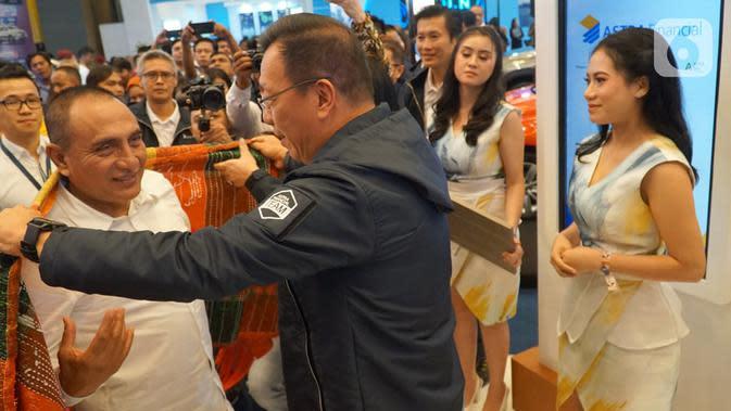 Gubernur Sumatera Utara Edi Rahmayadi saat mengunjungi booth dan dikenakan ulos oleh Project Director GIIAS 2019 Gunawan Salim di GIIAS 2019 Medan, Rabu (23/10/2019). (Liputan6.com/HO/Eko)