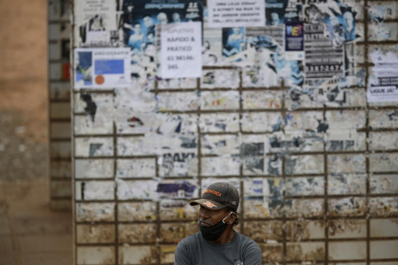 A man wearing a mask against the spread of the new coronavirus waits for a bus at a bus station in Valparaiso, Brazil, Wednesday, May 20, 2020. (AP Photo/Eraldo Peres)