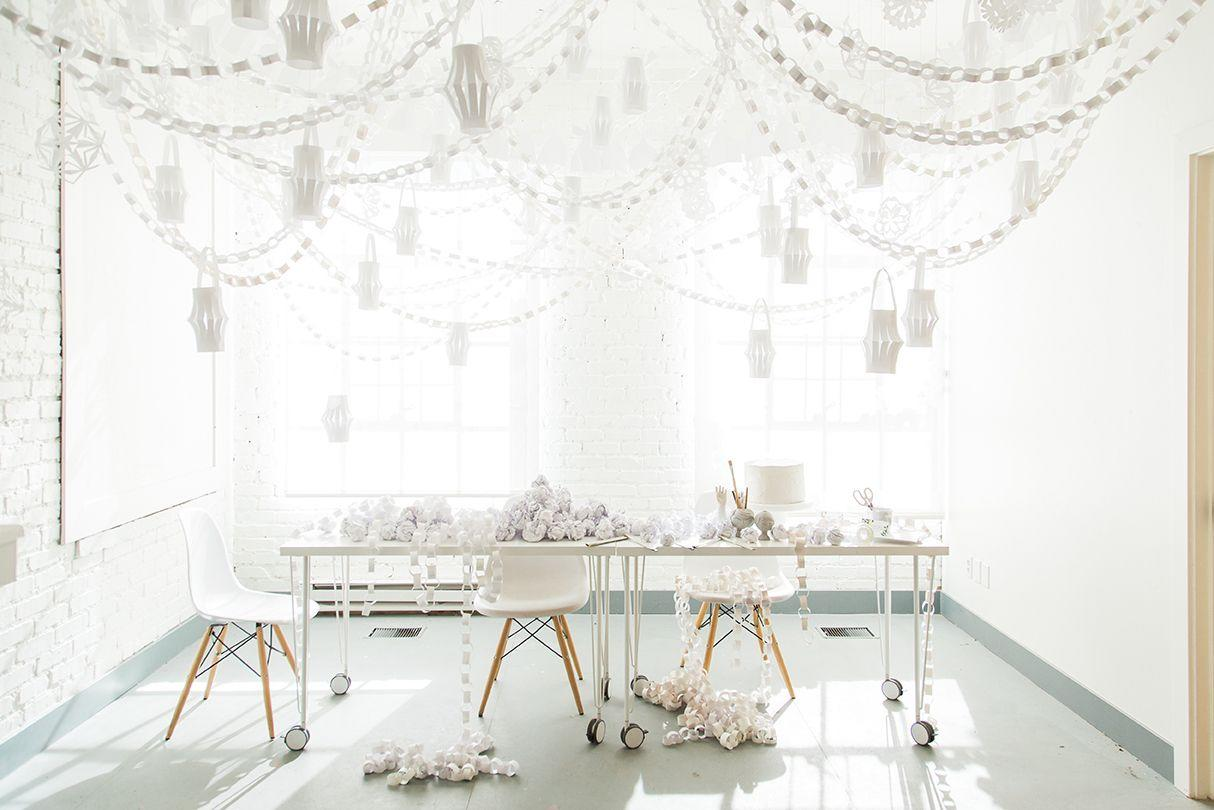 """<p>Use ordinary white office paper to create the most dreamy decor for your holiday gathering. Fold and cut each sheet of paper into a unique, symmetrical snowflake. Hang alongside copious paper chains and lanterns to complete the look.</p><p><a href=""""https://thehousethatlarsbuilt.com/2016/12/christmas-paper-office-party-decorations.html/"""" target=""""_blank""""><em>Get the tutorial at the House That Lars Built</em></a></p>"""