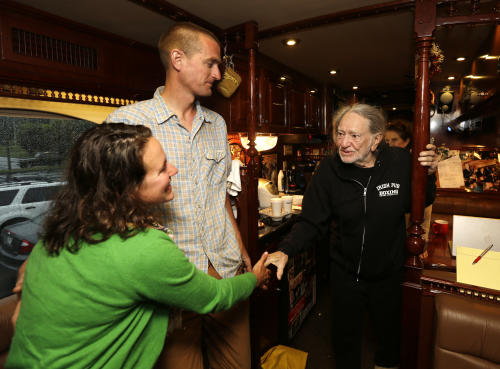 Cara Fraver, left, and her husband Luke Deikis of Quincy Farm in Easton, N.Y., meet country music artist Willie Nelson on his tour bus on Thursday, June 13, 2013, in Colonie, N.Y. Nelson is taking his annual Farm Aid benefit concert to upstate New York with an all-day festival of music and locally grown food in September. (AP Photo/Mike Groll)