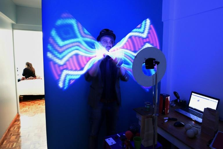 Magician Gustavo Pintos shakes a light-stick as he performs for an online birthday party hundreds of kilometers away from his home in Buenos Aires