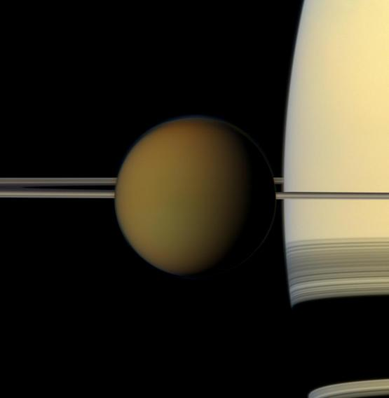 This undated true color image by the Cassini spacecraft released by NASA shows Saturn's largest moon, Titan, passing in front of the planet and its rings. A new study released Thursday, June 28, 2012 suggests there may be an ocean below Titan's frigid surface. (AP Photo/NASA)