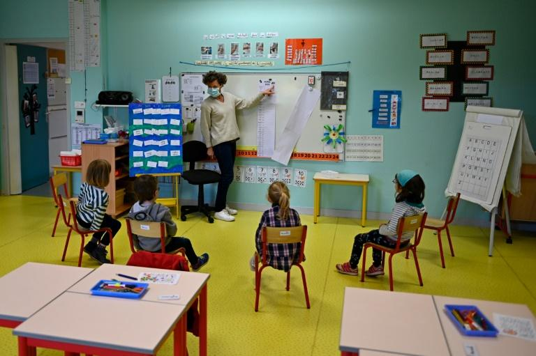 A mask-wearing teacher and some socially-distanced pupils at one reopened school in Bruz, near Rennes in northwest France