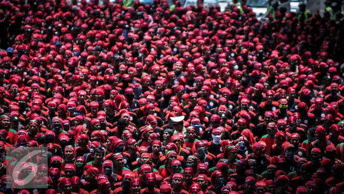 Ribuan buruh berjalan menuju Istana Negara, Jakarta, Kamis (29/9). Dalam aksinya mereka menolak Tax Amnesty serta menaikan upah minumum provinsi (UMP) sebesar Rp650 ribu per bulan. (Liputan6.com/Faizal Fanani)
